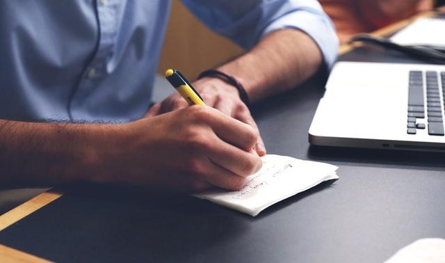 man writing notes